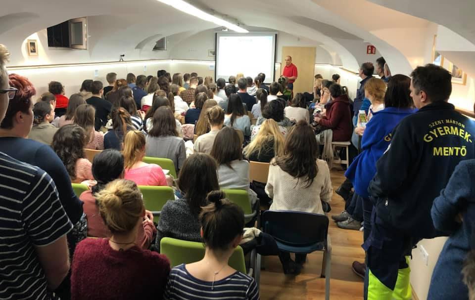 Hallgatók ülve és állva figyelik az előadó prezentációját az oktatóteremben.