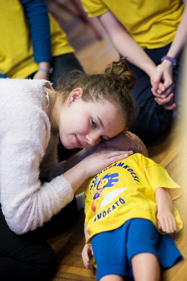 Egy kislány újraélesztést gyakorol egy fantombabán