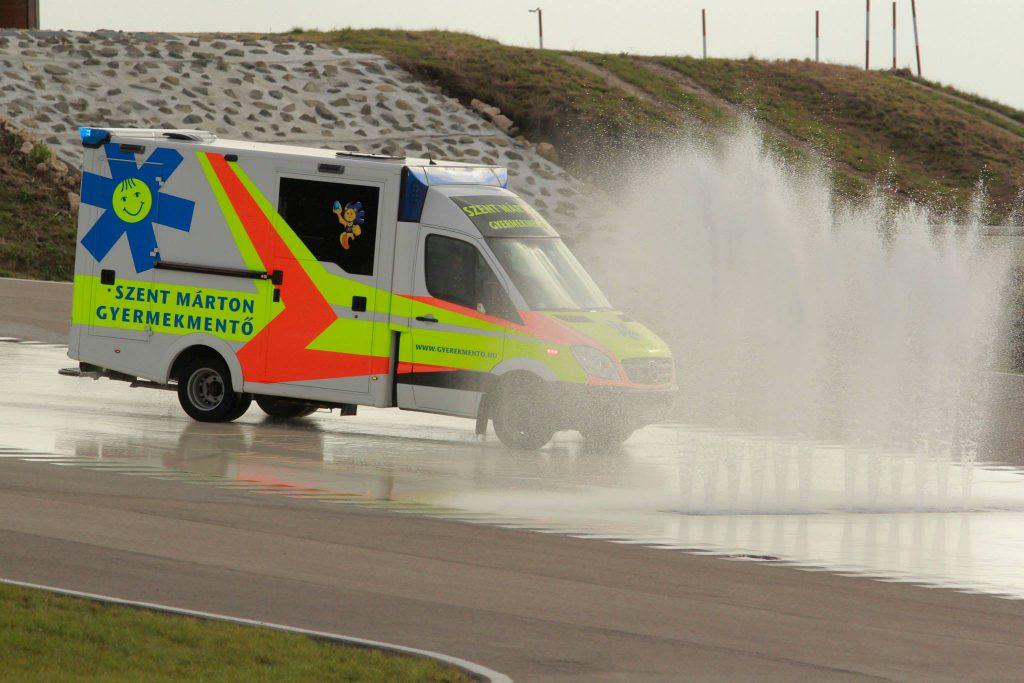 A Gyermekrohamkocsi egy vezetéstechnikai pálya vizes aszfaltján halad