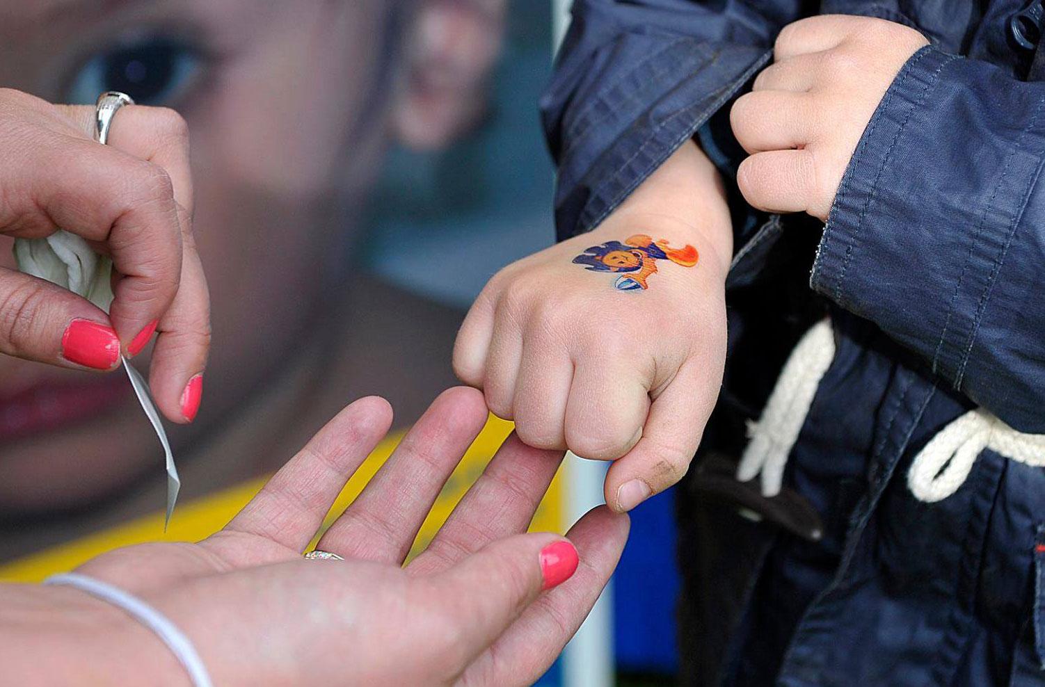 Mentő Mártonos matricát tetoválnak egy gyerek kézfejére
